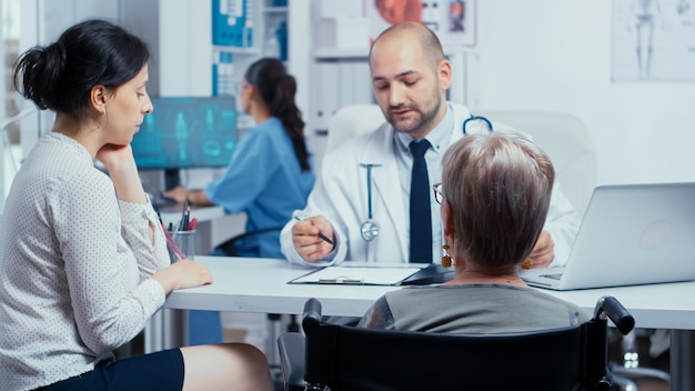 Kobieta na wózku inwalidzkim z córką na corocznej wizycie u lekarza. selektywne skupienie. leczenie osób niepełnosprawnych inwalidów w nowoczesnym prywatnym szpitalu lub klinice. medycyna i opieka zdrowotna