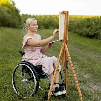 Kobieta na wózku inwalidzkim z płótna i malowanie palet na zewnątrz