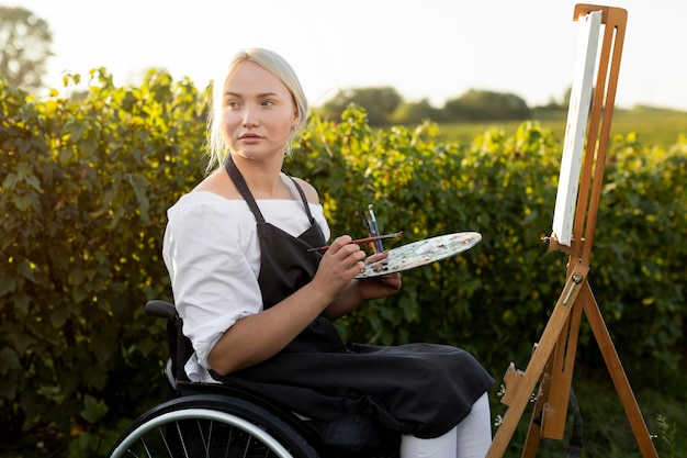 Kobieta na wózku inwalidzkim z płótnem i paletą na zewnątrz