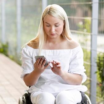 Kobieta na wózku inwalidzkim z smartphone
