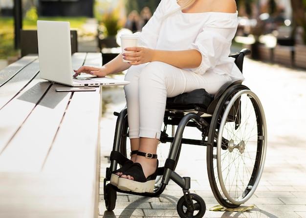 Kobieta na wózku inwalidzkim za pomocą laptopa na zewnątrz przy drinku