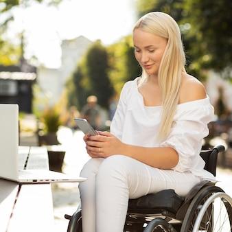 Kobieta na wózku inwalidzkim za pomocą smartfona na zewnątrz z laptopem