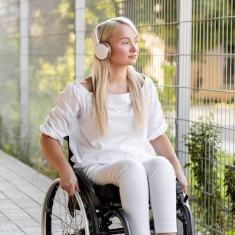 Kobieta na wózku inwalidzkim ze słuchawkami na zewnątrz