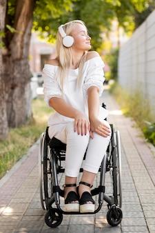 Kobieta na wózku inwalidzkim ze słuchawkami