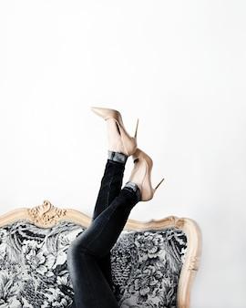 Kobieta na wysokich obcasach, leżąca na kanapie, trzymając nogi w górze, pozuje do modowej sesji zdjęciowej