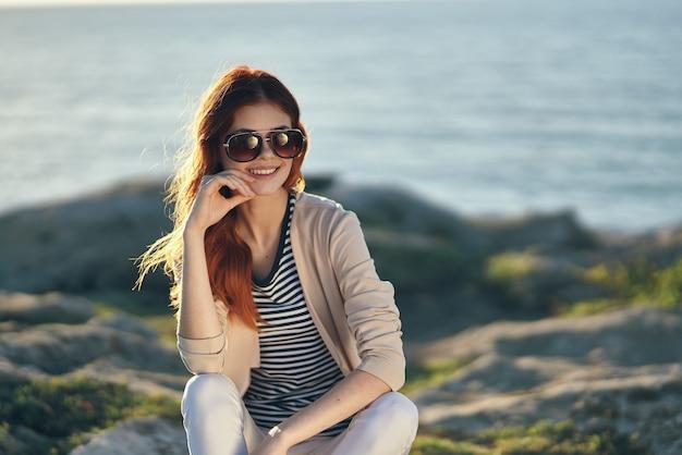 Kobieta na wysokim kamieniu w górach w pobliżu morza i okulary na twarzy letnie wakacje podróż