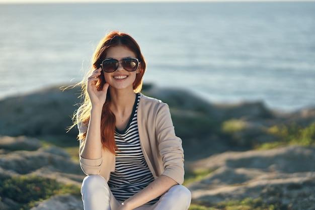 Kobieta na wysokim kamieniu w górach w pobliżu morza i okulary na twarzy