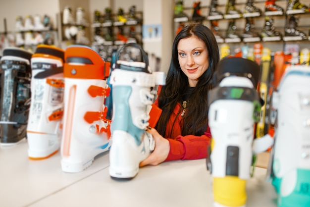 Kobieta na wystawie wybiera buty narciarskie lub snowboardowe, robi zakupy w sklepie sportowym.