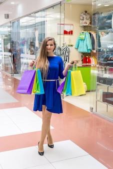 Kobieta na zakupach z dolarami i kolorowymi torbami