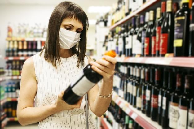 Kobieta na zakupy alkoholu w sklepie spożywczym i noszenie maski ochronnej