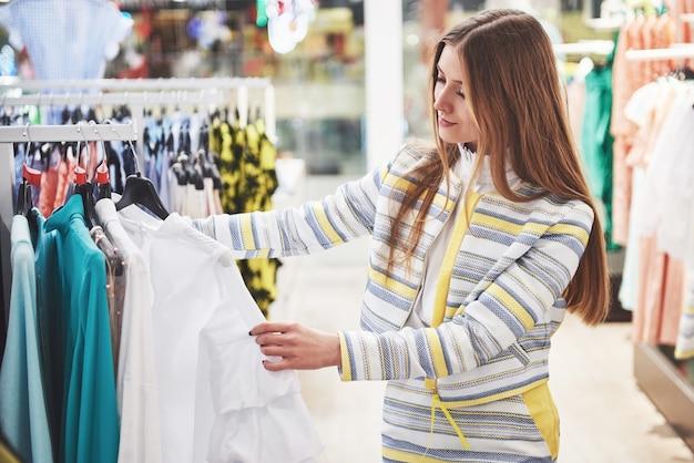 Kobieta na zakupy. kupujący oglądający ubrania w sklepie. piękny szczęśliwy uśmiechnięty kaukaski modelki.