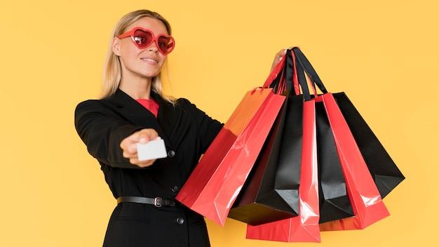 Kobieta na zakupy w czarny piątek pokazując torby i kupon