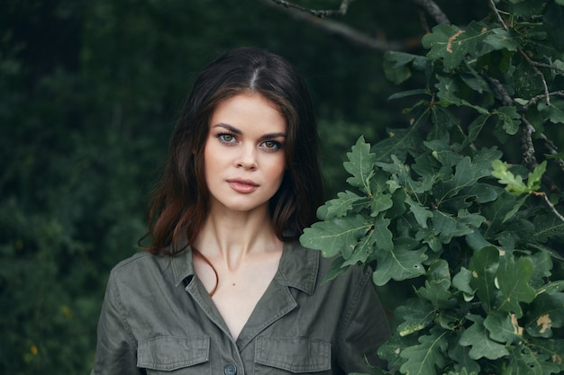 Kobieta na zewnątrz atrakcyjny wygląd zielone liście krzewów lato close-up