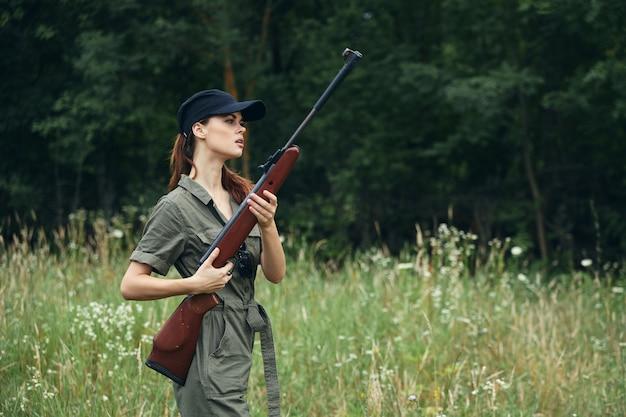 Kobieta na zewnątrz broni w zielony kombinezon podróży styl życia świeże powietrze tło lasu