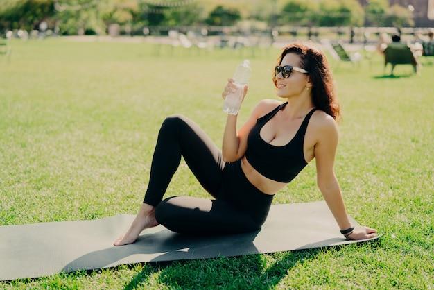 Kobieta na zewnątrz pije wodę z butelki siedząc na macie do jogi