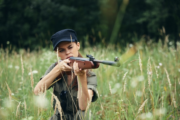 Kobieta na zewnątrz siedząc na broń trawa w rękach wzroku polowanie świeże powietrze