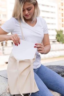 Kobieta na zewnątrz umieszczenie książki w jej torbie