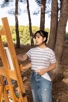 Kobieta na zewnątrz w malowaniu przyrody