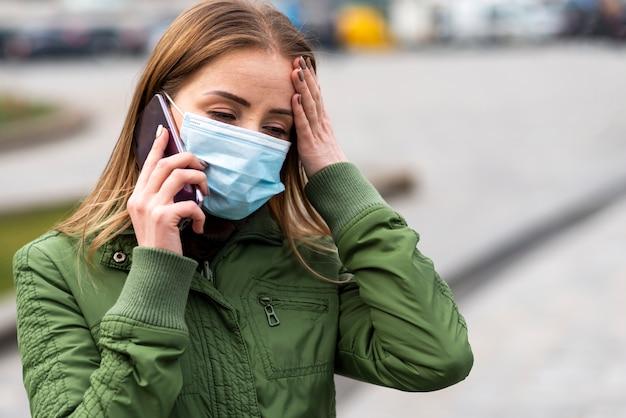 Kobieta na zewnątrz w masce i rozmawia przez telefon komórkowy