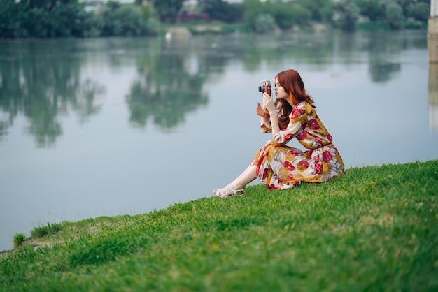 Kobieta na zewnątrz z aparatem na brzegu rzeki hobby wypoczynek.