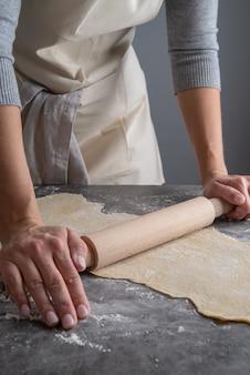 Kobieta naciskając ciasto makaronowe