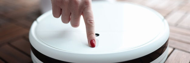 Kobieta naciskając przycisk w zbliżenie odkurzacz robota. koncepcja naprawy sprzętu agd