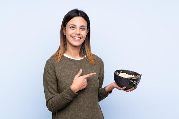 Kobieta nad niebieską ścianą i wskazując go, trzymając miskę makaronu pałeczkami