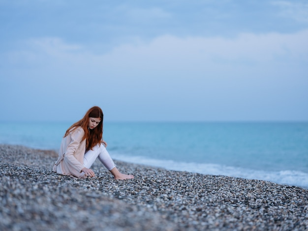 Kobieta nad oceanem piasek kamienie plaża model ciepły sweter spodnie. wysokiej jakości zdjęcie