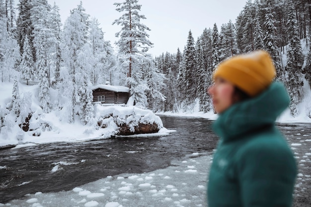Kobieta nad zamarzniętą rzeką w laponii, finlandia