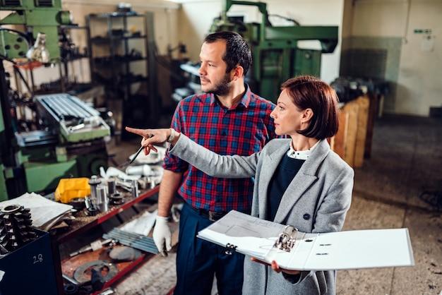 Kobieta nadzorca fabryki stojąc z mechanikiem i dyskusji