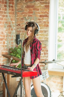 Kobieta nagrywa muzykę, śpiewając i grając na pianinie, stojąc w miejscu pracy na poddaszu lub w domu