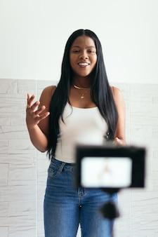 Kobieta nagrywa się swoim aparatem w domu