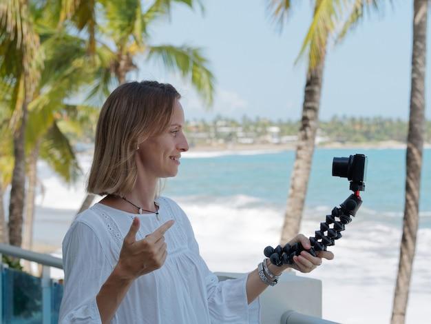 Kobieta nagrywająca blog podróżniczy na plaży. ocean i palmy w tle drzewa.