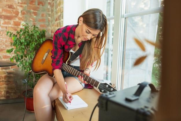 Kobieta nagrywająca muzykę, śpiewającą i grającą na gitarze, siedząc w miejscu pracy na poddaszu lub w domu