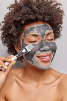 Kobieta nakłada glinianą maskę pędzlem kosmetycznym utrzymuje zamknięte oczy poddaje się zabiegom pielęgnacyjnym stoi nago lubi rozpieszczać zabiegi pozuje w pomieszczeniu.
