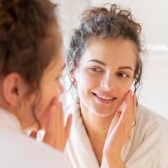 Kobieta nakłada krem na twarz, patrząc w lustro