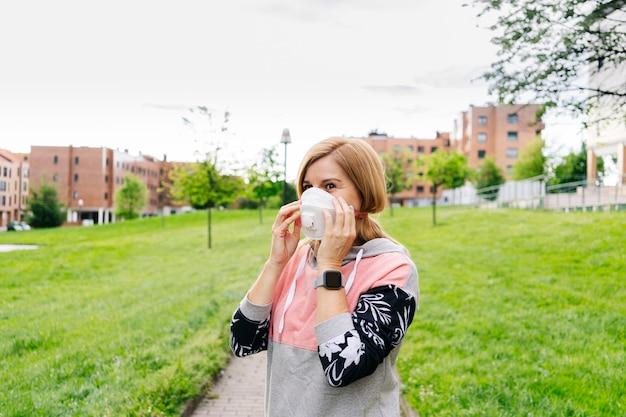 Kobieta nakłada maskę na twarz w parku z budynkami.
