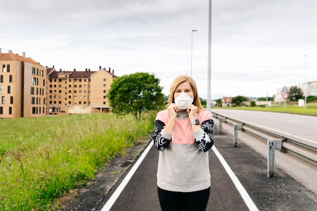 Kobieta nakłada maskę na twarz wokół miasta