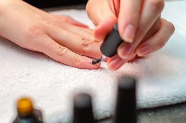 Kobieta nakłada na paznokcie podkład przed nałożeniem lakieru. zbliżenie dłoni.