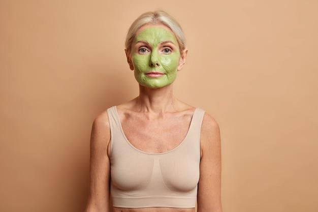 Kobieta nakłada odżywczą zieloną maseczkę na twarz używa produktów kosmetycznych