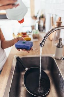 Kobieta nakłada środek czyszczący na gąbkę, aby umyć patelnię w zlewie kuchennym. ręczne mycie naczyń. zbliżenie.