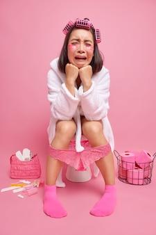 Kobieta nakłada wałki do włosów plastry upiększające czuje ból brzucha cierpi na biegunkę pozuje na muszli klozetowej w ubikacji odizolowanej nad różową ścianą ma zły humor nosi szlafrok zatopione majtki