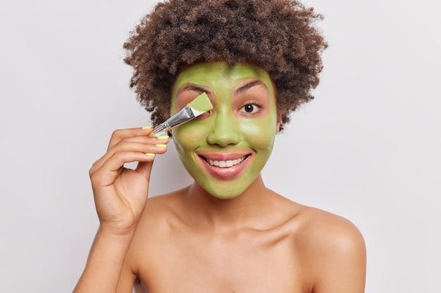 Kobieta nakłada zieloną, domową, naturalną maskę z pędzelkiem kosmetycznym, uśmiecha się, ząbkuje, stoi topless, ma zdrową skórę na białym tle