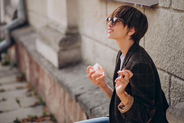 Kobieta nakładająca zapach na szyję