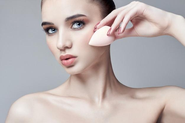 Kobieta nakładała makijaż gąbką na twarz. profesjonalny makijaż rękami. pielęgnacja skóry, kosmetyki naturalne. produkty do pielęgnacji skóry