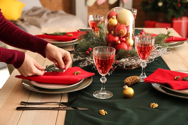Kobieta nakrywa do stołu na świąteczny obiad