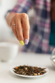 Kobieta nalewa aromatyczne zioła podczas przygotowywania herbaty