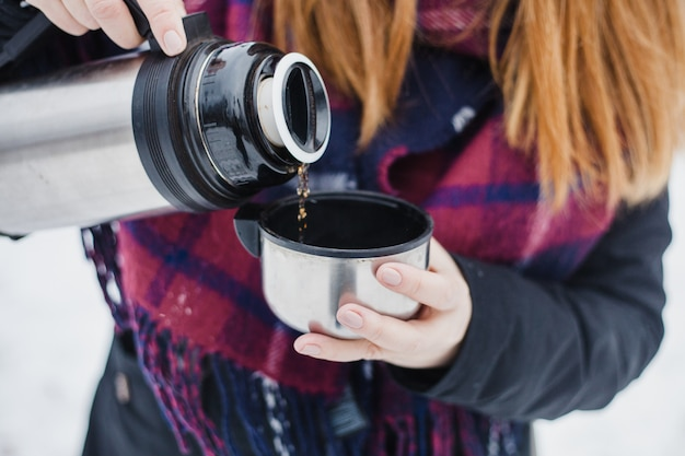 Kobieta nalewa gorącą herbatę lub napój z termosu, zimowy spacer, piesze wycieczki, zimowe, zimowe ubrania
