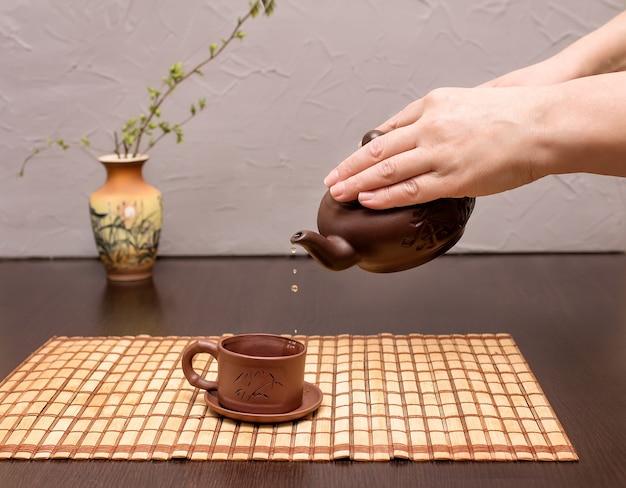 Kobieta nalewa herbatę z czajnika do filiżanki. chińska ceremonia parzenia herbaty. wazon z gałązką w tle w rozmyciu.