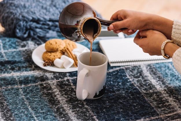 Kobieta nalewa napój w filiżance od cezve blisko ciastek i notepad